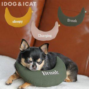 三日月型の枕で寝る犬